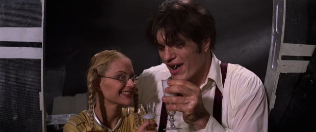 Out of character and out of place, Jaws and Dolly sharing a glass of bubbly